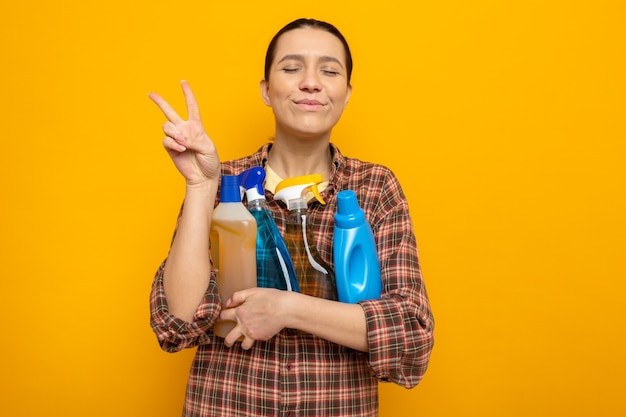 Młoda sprzątaczka w zwykłych ubraniach trzymająca środki czystości szczęśliwa i wesoła pokazująca znak v stojący nad pomarańczową ścianą