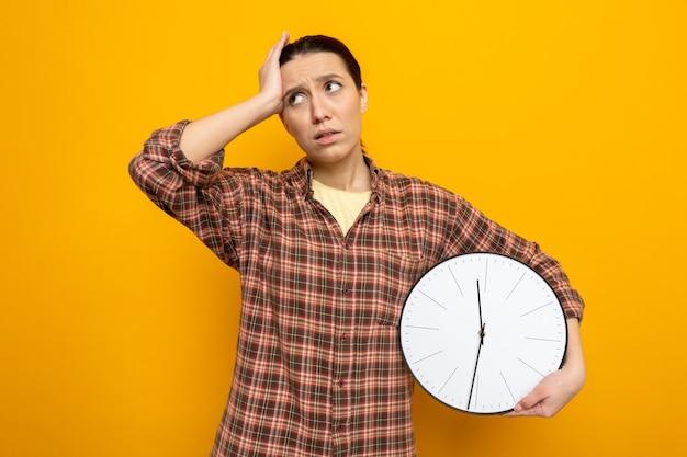 Młoda sprzątaczka w zwykłych ubraniach, trzymająca zegar, wyglądająca na zdezorientowaną i bardzo zaniepokojoną, z ręką na głowie