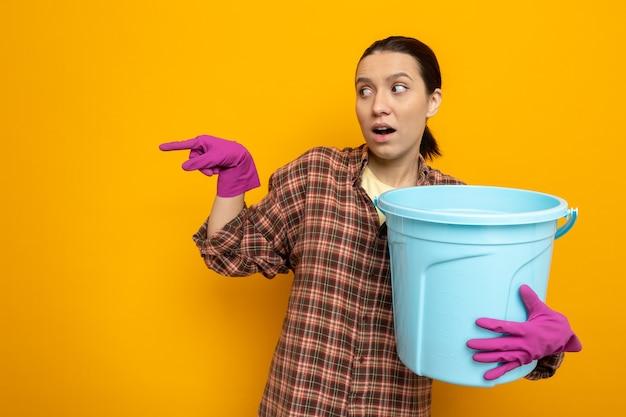 Młoda sprzątaczka w zwykłych ubraniach w gumowych rękawiczkach, trzymająca wiadro lookign na bok, zmartwiona, wskazując palcem wskazującym w bok, stojąc na pomarańczowo