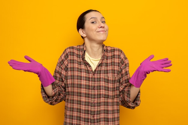 Młoda sprzątaczka w zwykłych ubraniach w gumowych rękawiczkach uśmiecha się rozkładając ręce na boki stojąc na pomarańczowo