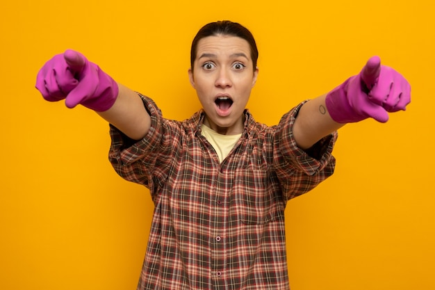 Młoda sprzątaczka w zwykłych ubraniach w gumowych rękawiczkach wygląda na zaskoczoną, wskazując palcami wskazującymi z przodu, stojąc nad pomarańczową ścianą