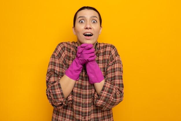 Młoda sprzątaczka w zwykłych ubraniach w gumowych rękawiczkach zdumiona i zaskoczona rękami razem czekającymi na coś pozytywnego stojącego nad pomarańczową ścianą