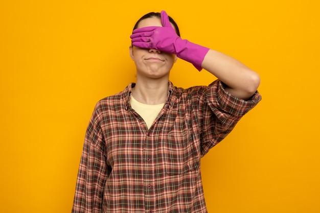 Młoda sprzątaczka w zwykłych ubraniach w gumowych rękawiczkach ze stożkowymi oczami z ręką stojącą na pomarańczowo