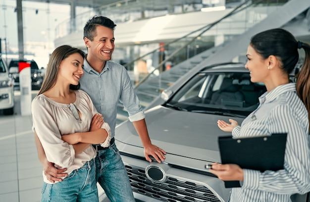 Młoda sprzedawczyni pokazuje parze samochód w salonie samochodowym. kupno lub wypożyczenie samochodu.