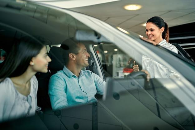 Młoda sprzedawczyni pokazuje zakochanej parze samochód w salonie samochodowym. kupno lub wypożyczenie samochodu.