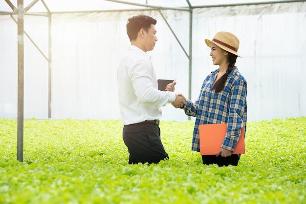 Młoda średniorolna azjatykcia kobiety chwiania ręka z biznesmenem w hydroponiki szklarnianym jarzynowym organicznie gospodarstwie rolnym.