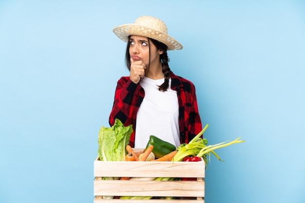 Młoda średniorolna kobieta trzyma świeżych warzywa w drewnianym koszu ma wątpliwości i wprawiać w zakłopotanie twarzy wyrażenie