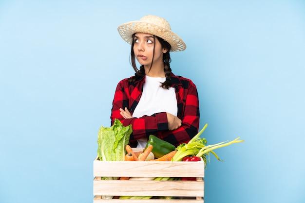 Młoda średniorolna kobieta trzyma świeżych warzywa w drewnianym koszu z zmieszanym twarzy wyrażeniem