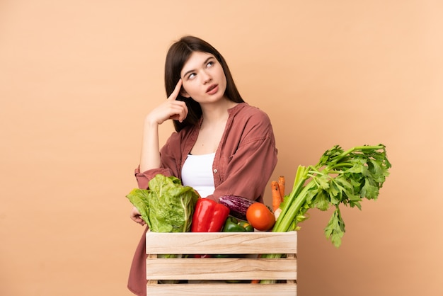 Młoda średniorolna kobieta z świeżo ukradzionymi warzywami w pudełku ma wątpliwości i główkowanie