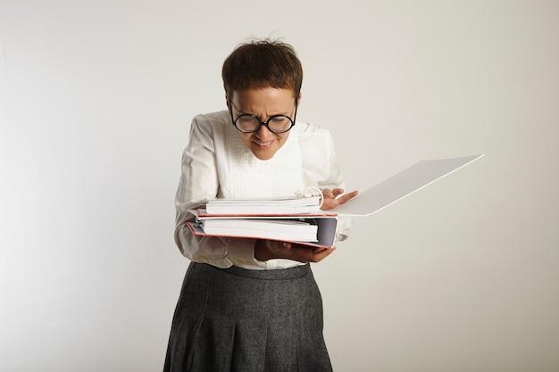 Młoda, staromodna wyglądająca nauczycielka w okrągłych czarnych okularach mruży oczy z niedowierzaniem na stronie wewnątrz jednego z dwóch segregatorów, które trzyma na białym tle.