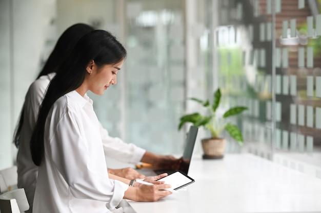 Młoda startupowa grupa biznesowa pracuje jako zespół, aby znaleźć rozwiązanie problemu i za pomocą tabletu z białym ekranem.