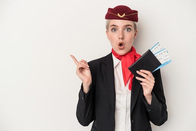 Młoda stewardessa kaukaska kobieta trzyma paszport na białym tle wskazujący na bok