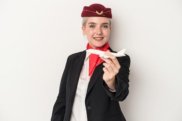 Młoda stewardessa kaukaska kobieta trzyma samolot na białym tle