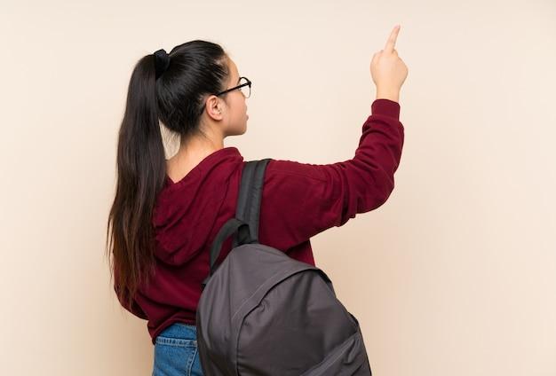 Młoda studencka azjatycka dziewczyny kobieta nad odosobnioną ścianą wskazuje z powrotem z palcem wskazującym