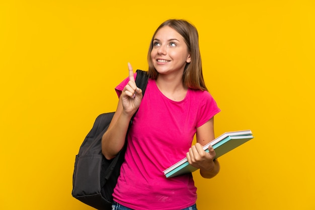 Młoda studencka dziewczyna nad odosobnioną kolor żółty ścianą zamierza realizować rozwiązanie podczas gdy podnoszący palec w górę