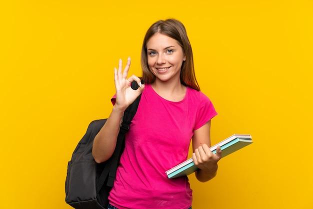 Młoda studencka dziewczyna nad odosobnionym kolorem żółtym pokazuje ok znaka z palcami