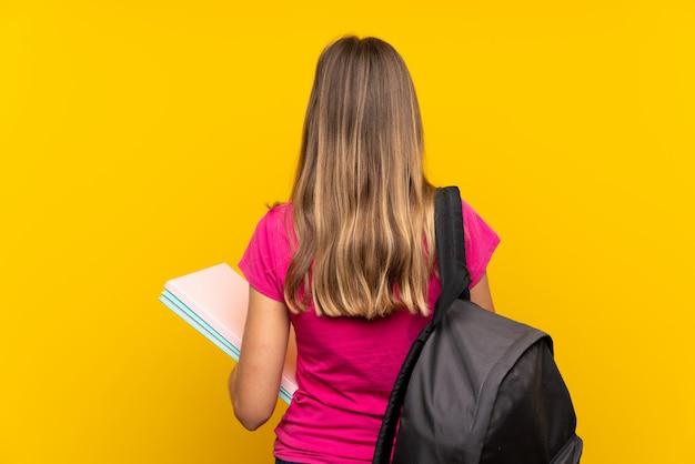 Młoda studencka dziewczyna nad odosobnionym kolorem żółtym w tylnej pozyci