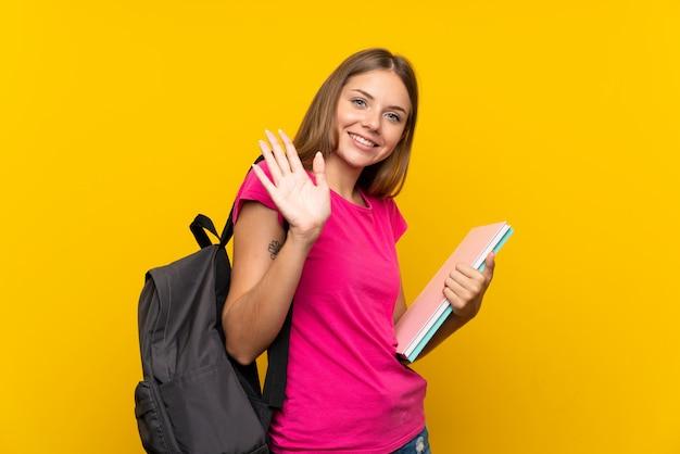 Młoda studencka dziewczyna nad odosobnionym żółtym salutować z ręką z szczęśliwym wyrażeniem
