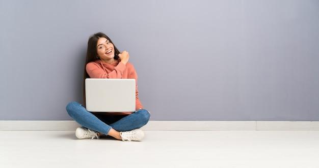 Młoda studencka dziewczyna świętuje zwycięstwo z laptopem na podłoga