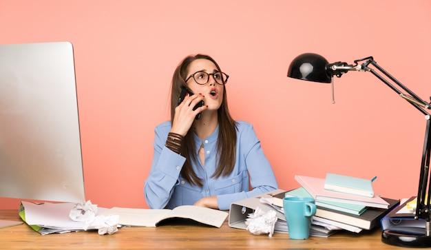 Młoda studencka dziewczyna utrzymuje rozmowę z telefonem komórkowym