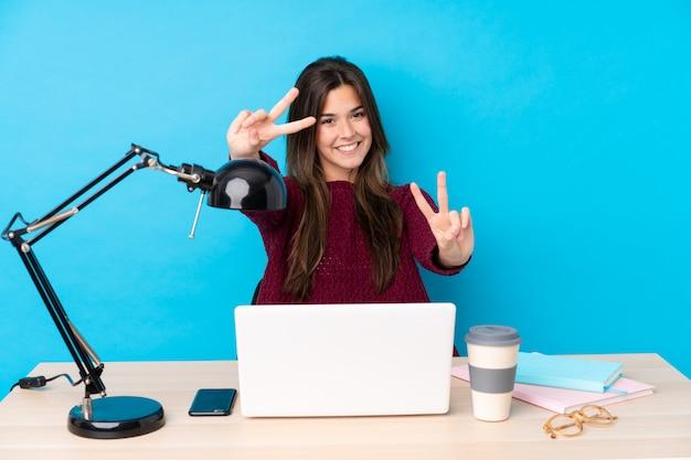 Młoda studencka dziewczyna w miejscu pracy nad błękit ścianą