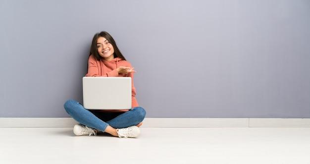 Młoda studencka dziewczyna z laptopem na podłodze rozciąga ręce na bok za zaproszenie