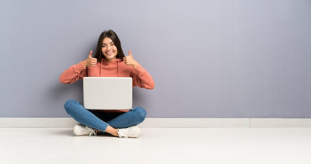 Młoda studencka dziewczyna z laptopem na podłoga daje aprobata gestowi