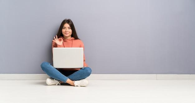 Młoda studencka dziewczyna z laptopem na podłoga pokazuje ok znaka z palcami