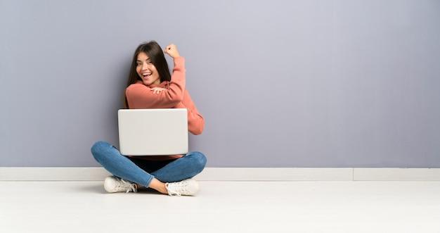 Młoda studencka dziewczyna z laptopem na podłoga robi silnemu gestowi