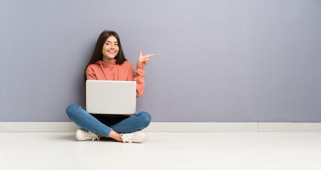 Młoda studencka dziewczyna z laptopem na podłogowym wskazuje palcu strona