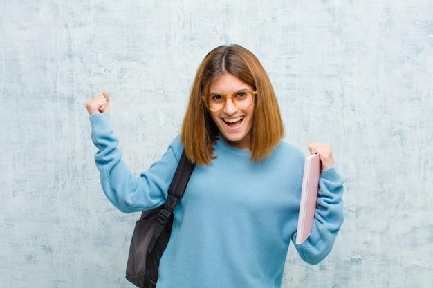 Młoda studencka kobieta czuje się szczęśliwy zdziwiony i dumny krzyczeć sukces z wielkim uśmiechem i świętować