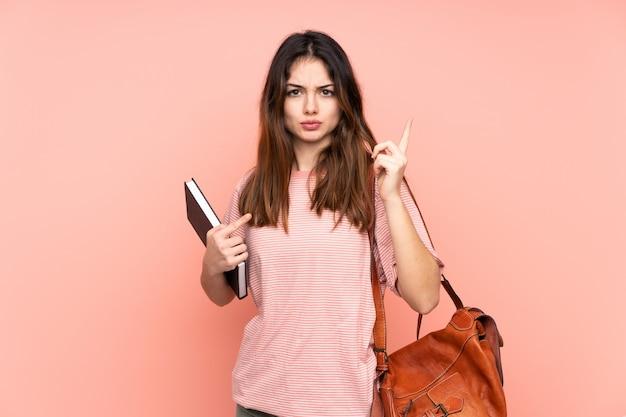 Młoda studencka kobieta idzie na uniwersytet przez różowy śmiech ściany