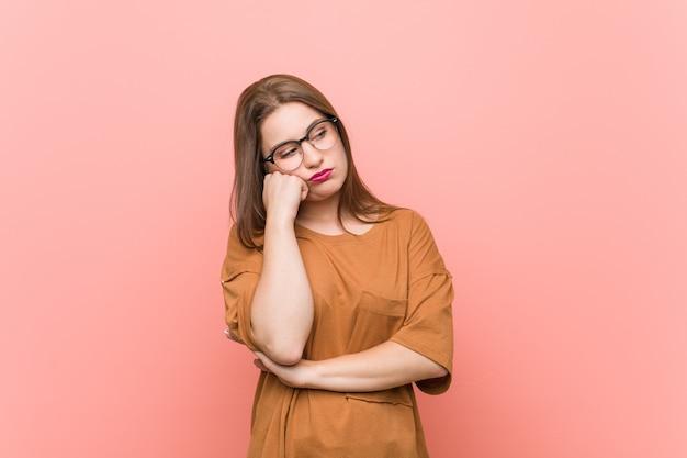 Młoda studencka kobieta jest ubranym eyeglasses który czuje smutny i zadumany, patrzeje kopii przestrzeń.