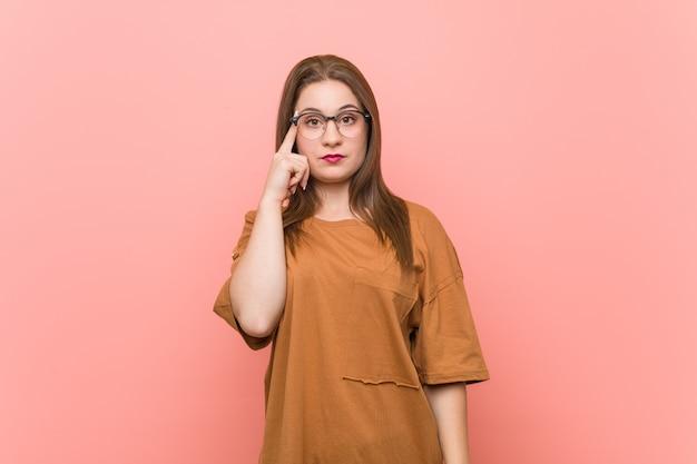 Młoda studencka kobieta jest ubranym eyeglasses wskazuje świątynię z palcem, główkowanie, skupiający się na zadaniu.