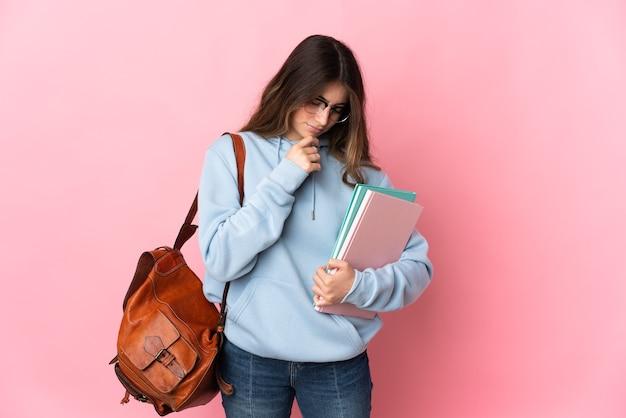 Młoda studencka kobieta na różowym tle ma wątpliwości