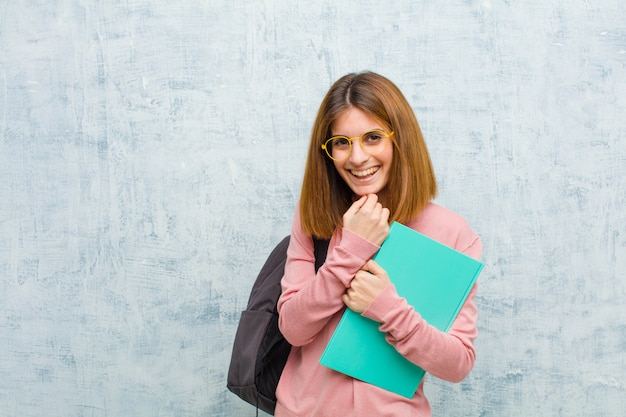 Młoda studencka kobieta ono uśmiecha się, cieszy się życie, czuje się szczęśliwy, przyjazny, zadowolony i beztroski, z ręką na brodzie ściany grunge