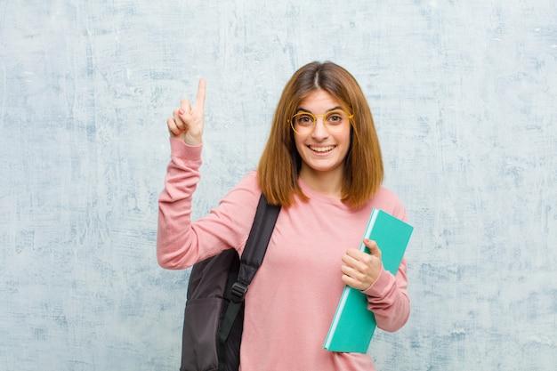 Młoda studencka kobieta ono uśmiecha się radośnie i szczęśliwie, wskazujący w górę z jedną ręką kopiować przestrzeń przeciw grunge ściany tłu