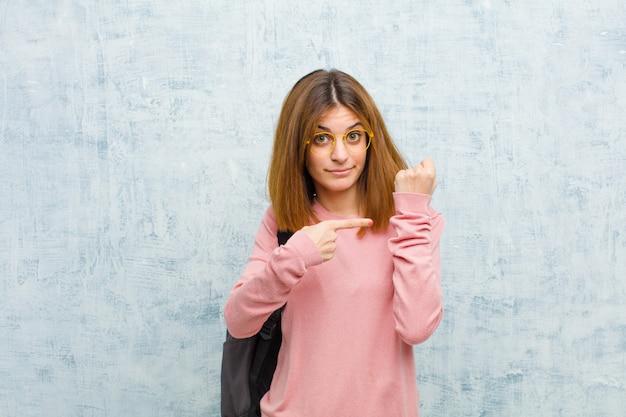 Młoda studencka kobieta, patrząc niecierpliwie i gniewnie, wskazując na zegarek, prosząc o punktualność, chce być na ścianie grunge czasu