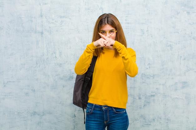 Młoda studencka kobieta patrzeje poważną i niezadowoloną z obu palcami skrzyżowanymi do przodu w odrzuceniu, prosząc o ciszę przeciwko grunge