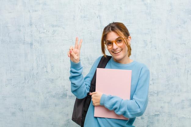 Młoda studencka kobieta patrzeje szczęśliwy, ufny i godny zaufania, uśmiecha się zwycięstwo znaka i pokazuje, z pozytywną postawą przeciw grunge ściany tłu