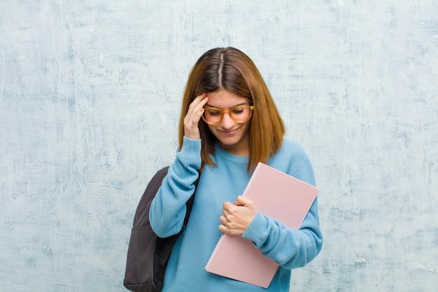 Młoda studencka kobieta patrzeje zestresowana i sfrustrowana, pracuje pod presją z bólem głowy i niepokoi się problemami
