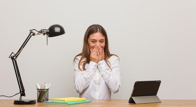 Młoda studencka kobieta pracuje jej biurko śmia się z czegoś, zakrywający usta rękami
