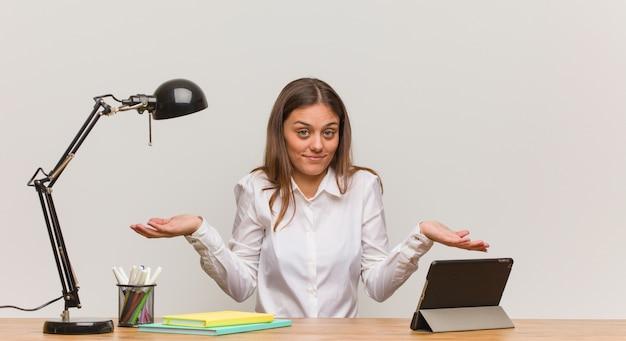 Młoda studencka kobieta pracuje na jej biurku wątpić i wzrusza ramionami ramiona