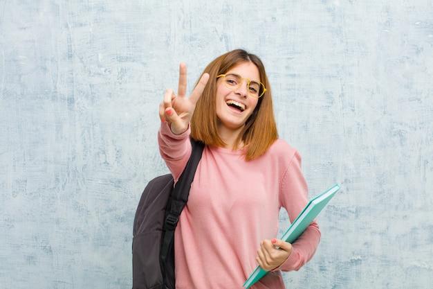 Młoda studencka kobieta uśmiechnięta i patrzeje życzliwa, pokazuje numer dwa lub drugi z ręką do przodu, odliczający w dół