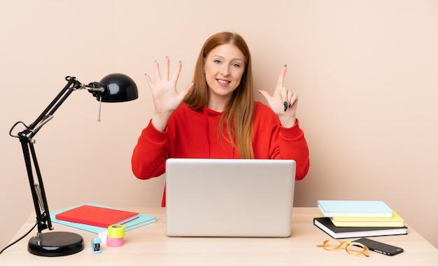 Młoda studencka kobieta w miejscu pracy z laptopem liczy siedem z palcami