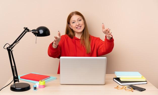 Młoda studencka kobieta w miejscu pracy z laptopem przedstawia ręka i zaprasza