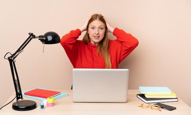 Młoda studencka kobieta w miejscu pracy z laptopem udaremniającym i bierze ręki na głowie
