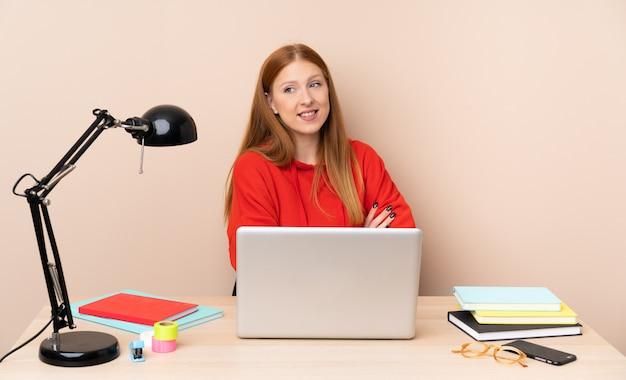 Młoda studencka kobieta w miejscu pracy z laptopem z rękami krzyżować i szczęśliwy