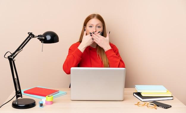 Młoda studencka kobieta w miejscu pracy z laptopem zakrywa usta z rękami