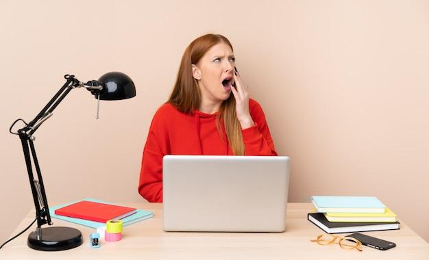Młoda studencka kobieta w miejscu pracy z laptopem ziewa i zakrywa szeroko otwarte usta ręką